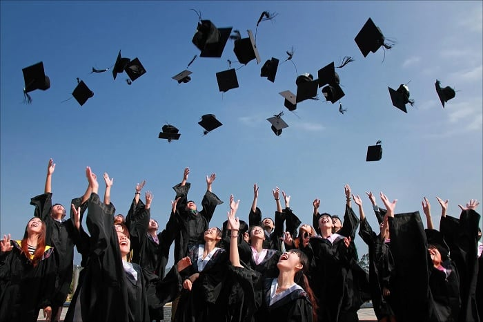University Graduates Throwing Hats In Air
