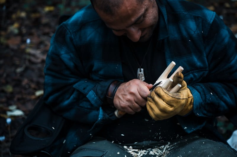 Close,Up,Of,Man,Carving,Branch,With,Knife,In,Nature