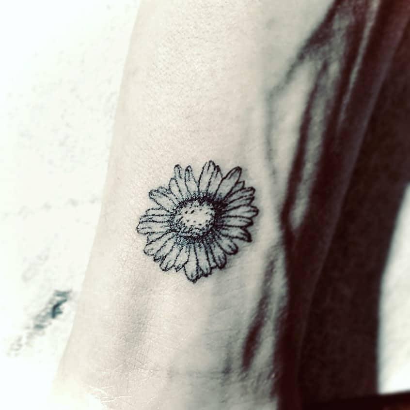 Wrist tattoo black and grey fine line daisy
