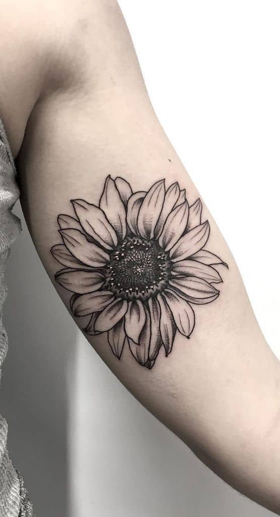 medium-sized black and grey tattoo on woman's forearm of realistic sunflower with white highlights