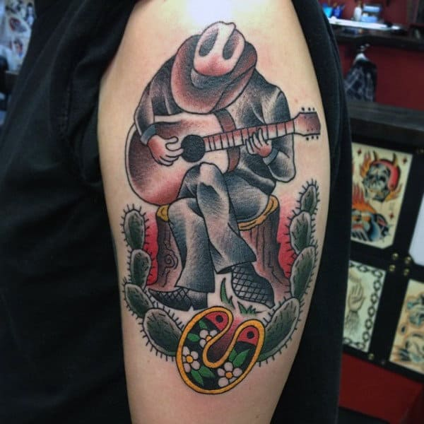American Traditional Style Tattoo Of Western Man In Desert Playing Guitar On Mans Bicep