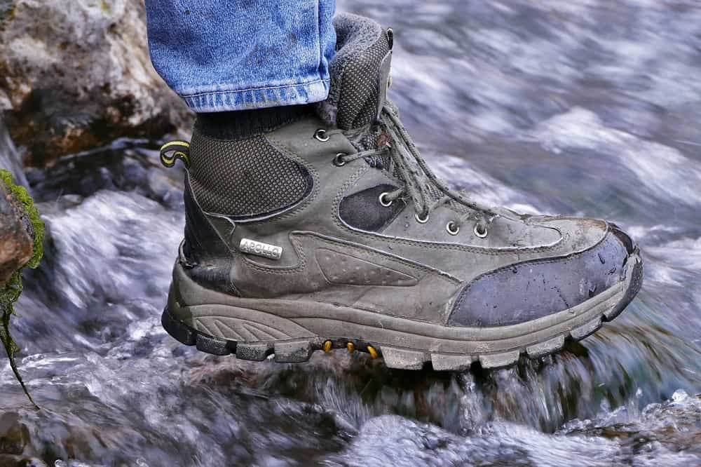 man wearing apollo hiking shoes crossing water outdoor