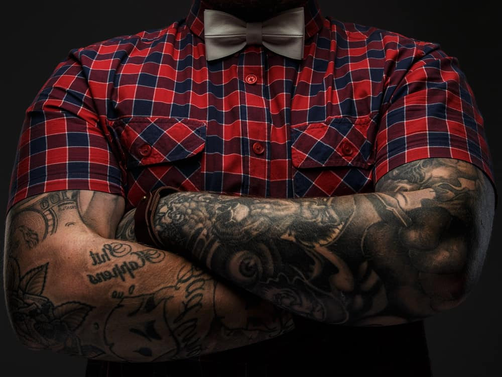 A pair of man's crossed arms that are covered in tattoos