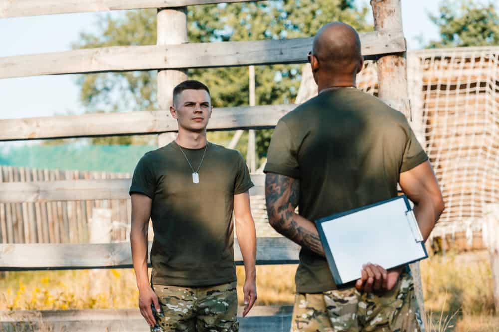 american tactical instructor with notepad and young soldier in military uniform on range