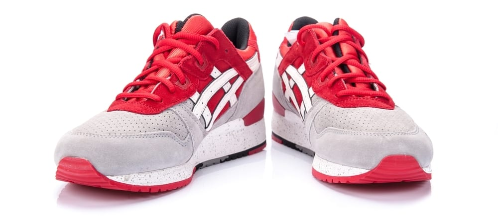 asics red and gray shoes on white surface