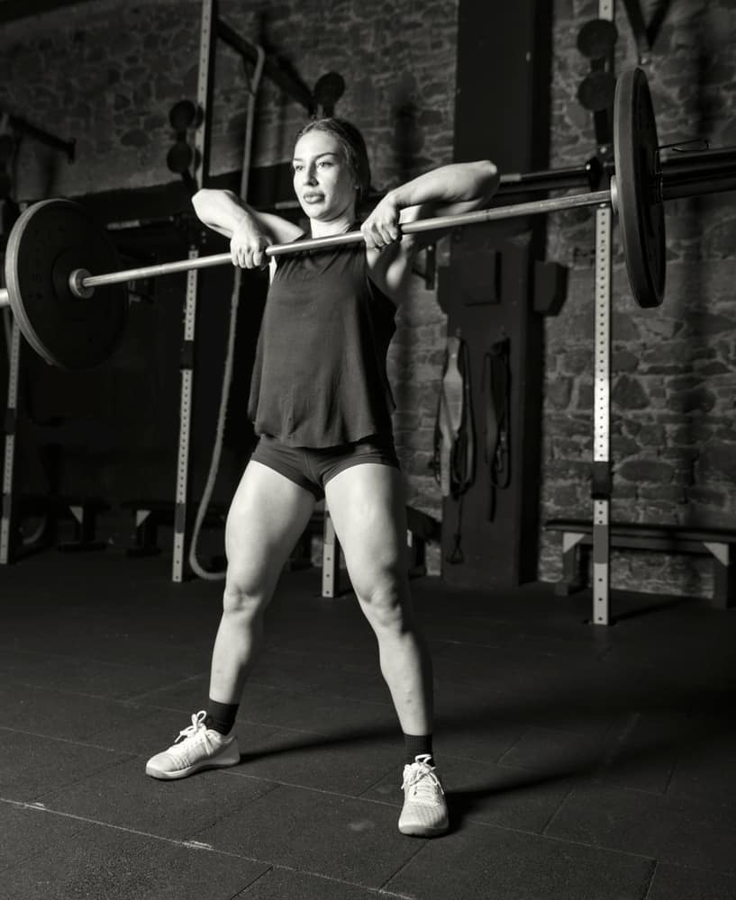 women athlete practicing high pull exercise in gym