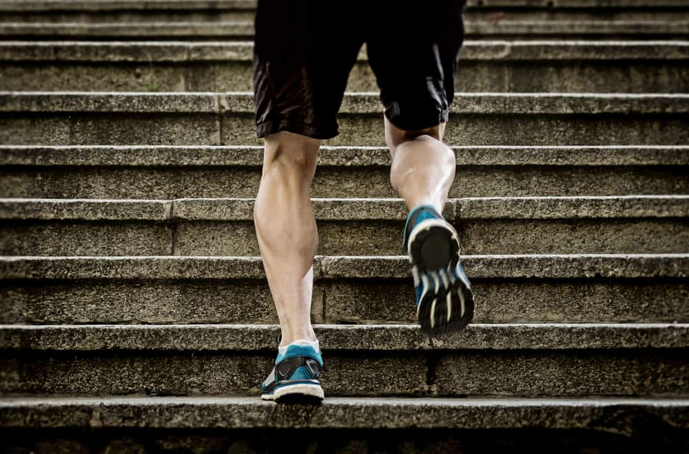 athletic legs of young sport man running on staircase steps