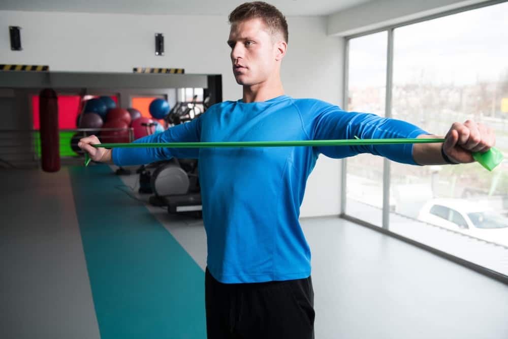 attractive man exercising with resistance band in gym