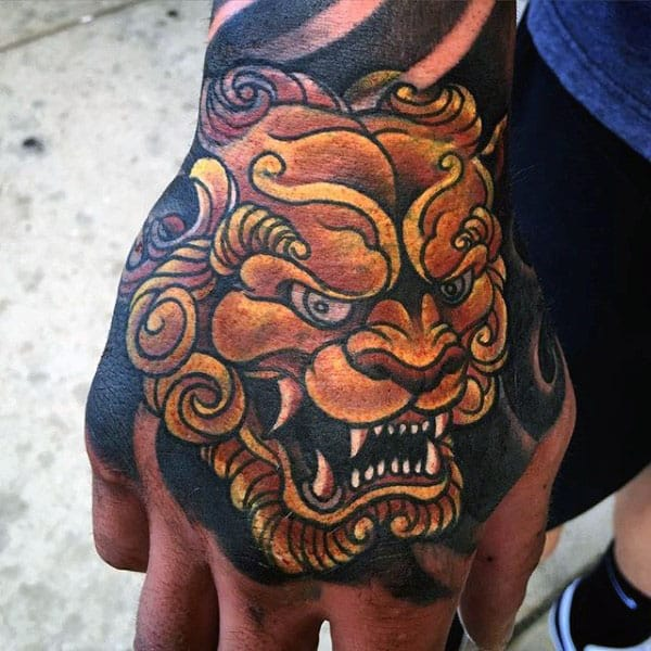 Awesome Gold Foo Dog Hand Tattoo On Male