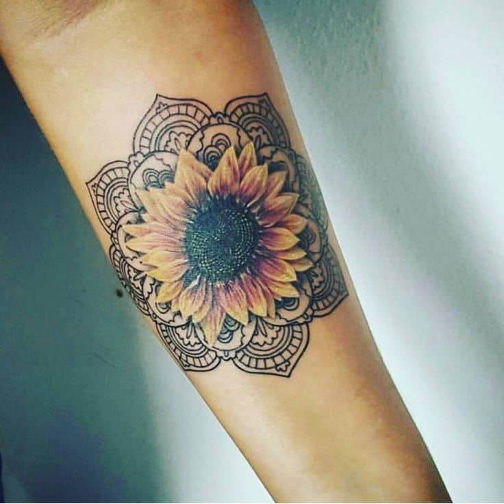 medium-sized black and color tattoo on forearm of realistic sunflower inside an ornamental mandala
