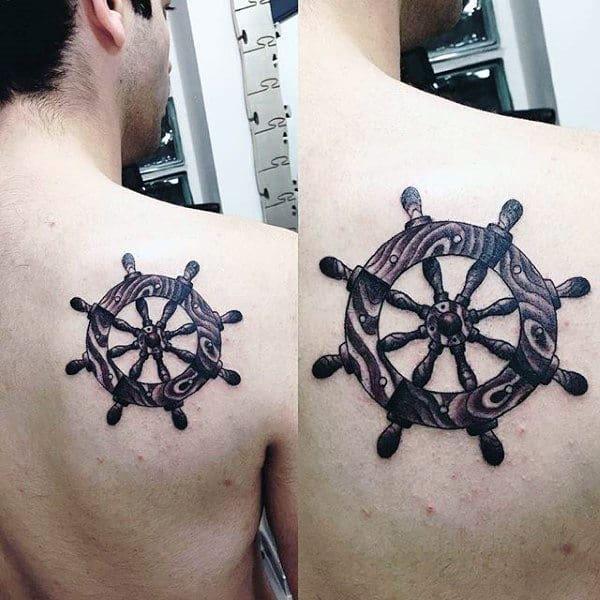Back Of Shoulder Ship Wheel Tattoo On Man With Black Ink