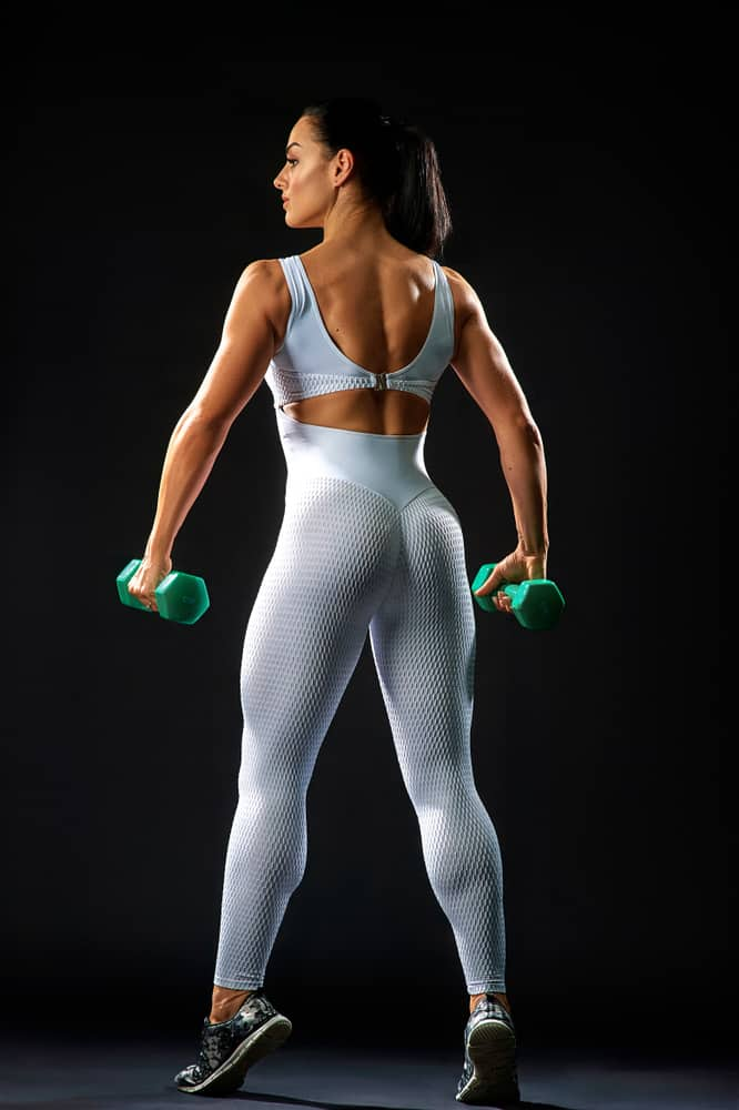 back view of muscular lady in white sportswear holding dumbbells