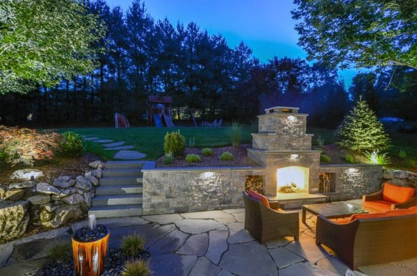 Backyard Landscaping Design With Outdoor Fireplace Made Of Cut Stone
