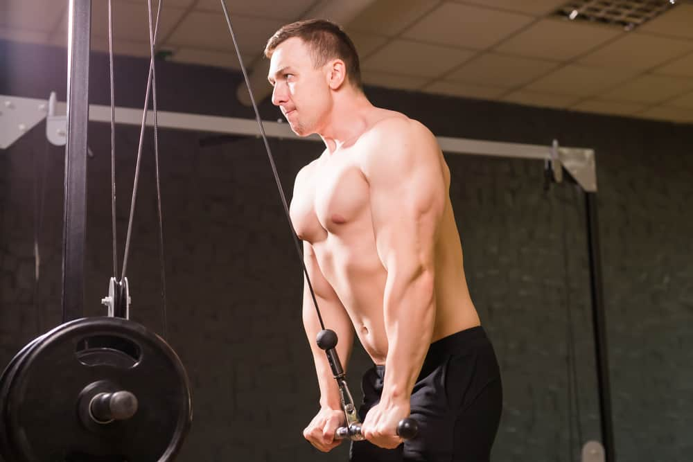 young man bar pushdown exercise in gym