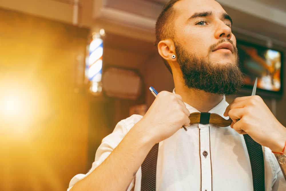 young handsome bearded barber straightens his bow tie