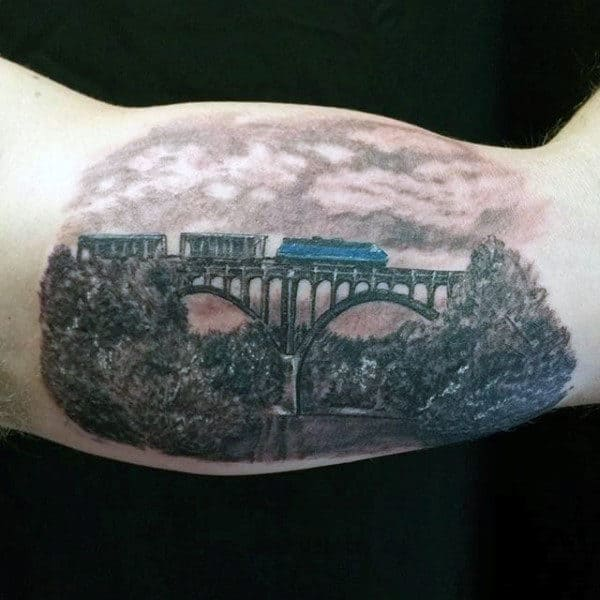 Bicep Train And Bridge Tattoo For Men