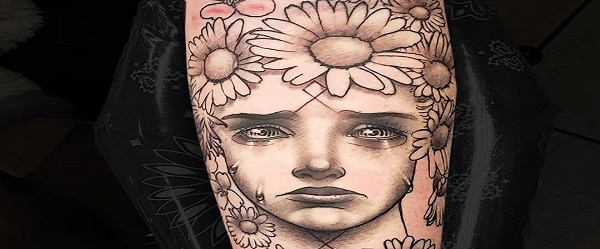 Forearm tattoo large surreal black and grey crying May Queen framed by daisies