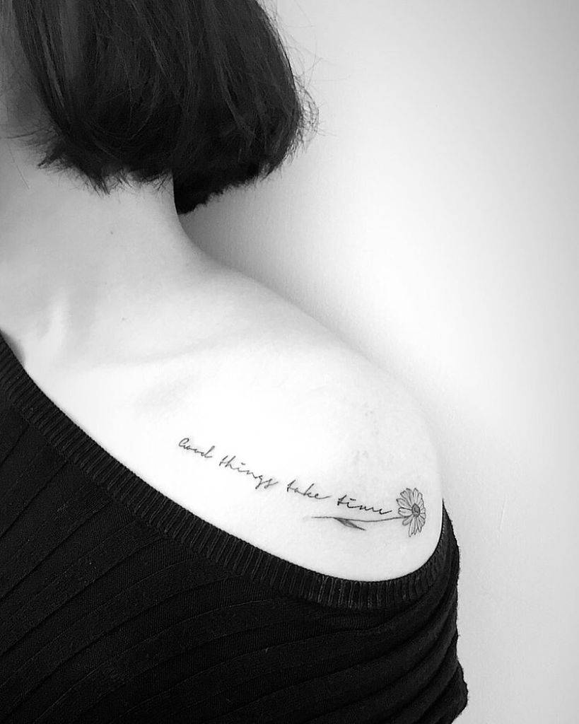 Shoulder tattoo small black and grey cursive script 'Good things take time' leading to fine line daisy