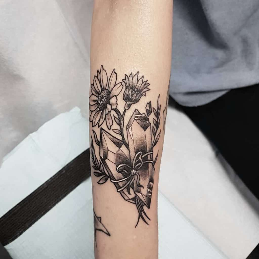 Forearm tattoo black and grey daisies and crystals