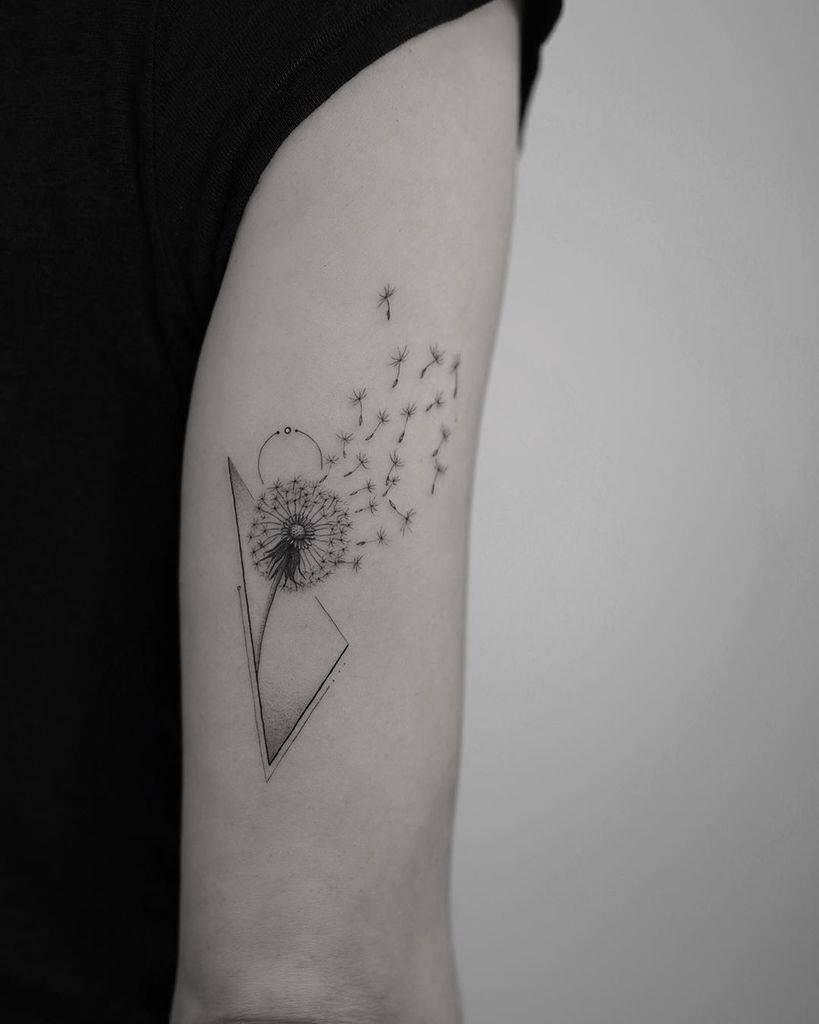 black and grey flying dandelion tattoo