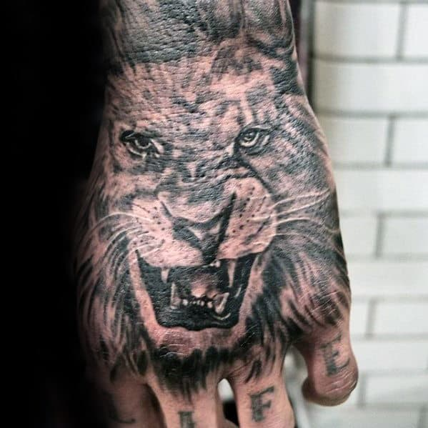 Black And Grey Male Lion Hand Tattoo