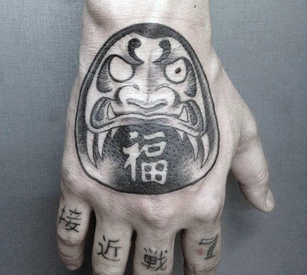 Black And Grey Shaded Daruma Doll Hand Tattoo On Man