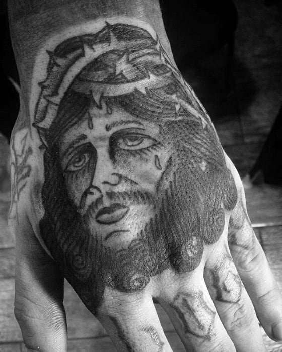 Black And Grey Shaded Traditional Jesus Male Hand Tattoo