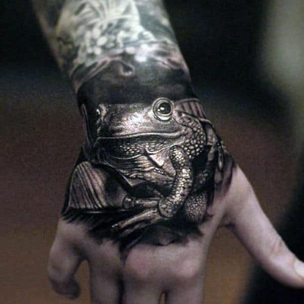 Black And White Ink Shaded Realistic 3d Male Hand Frog Tattoos