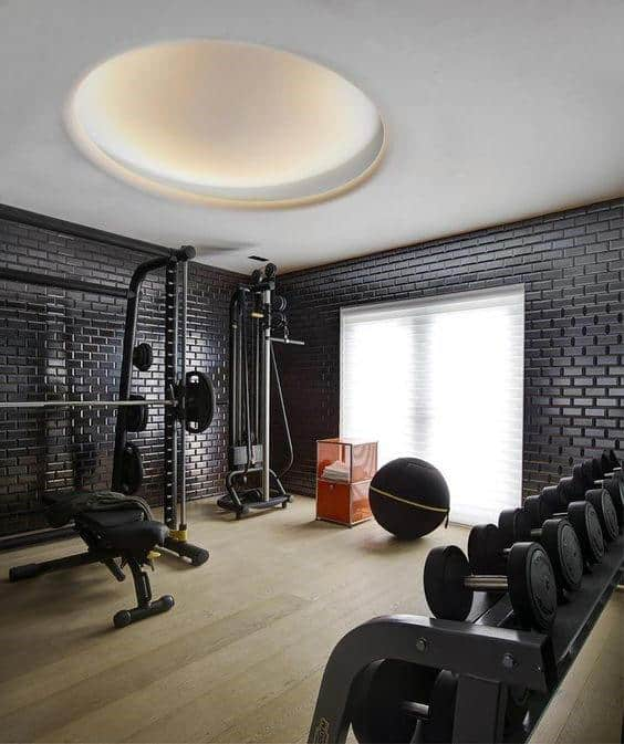 black brick wall home gym with hardwood flooring design ideas - In Home Gym Designs