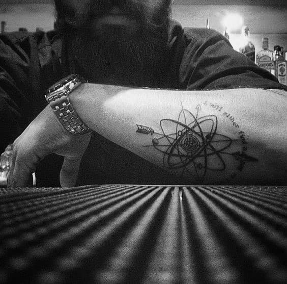 Black Ink Atom Out Of Forearm Tattoo On Man