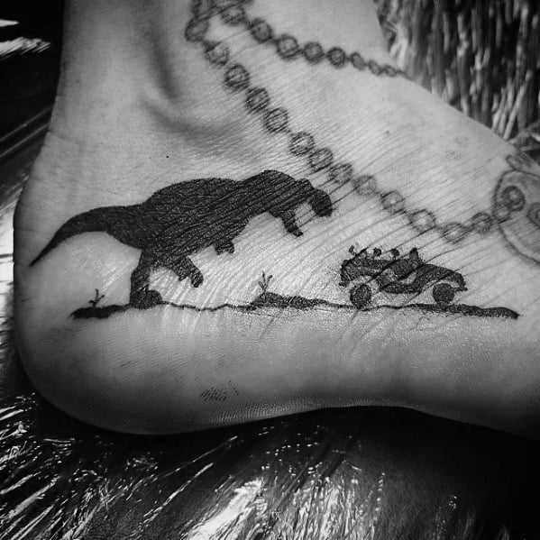 Black Ink Dinosaur Chasing Jeep Side Of Foot Male Jurassic Park Tattoo Designs