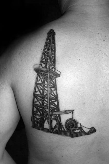 Black Ink Mens Oilfield Well Tattoo On Upper Side Of Back