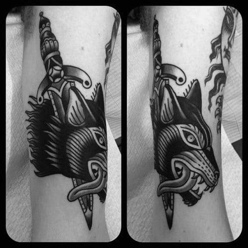 Black Ink Wolf Head With Dagger Male Traditional Arm Tattoo Ideas
