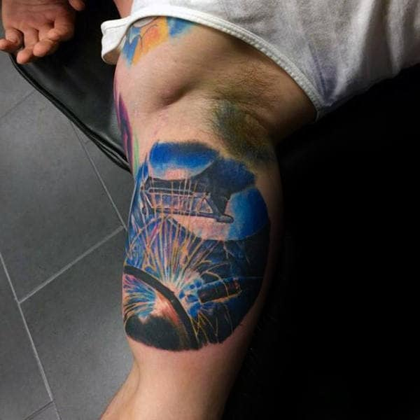 Blue Ink Guys Welding Bicep Tattoo With Flying Sparks Design