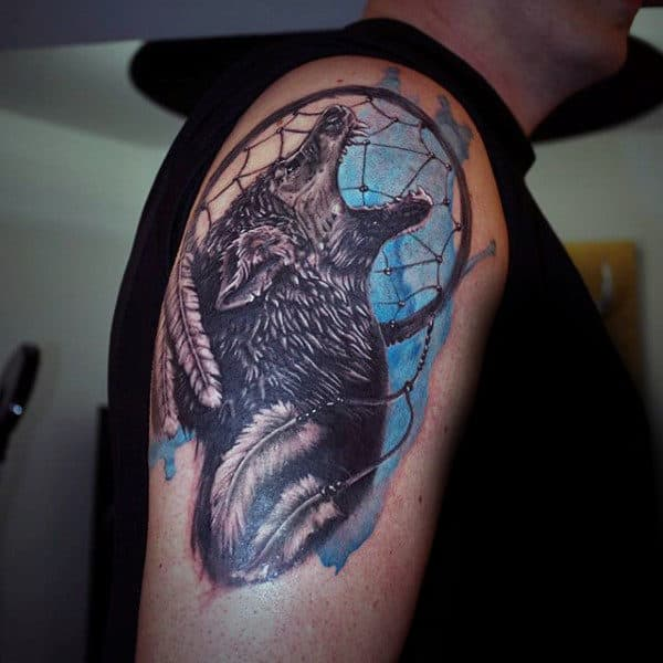 Blue Watercolor Ink Dreamcatcher Upper Arm Tattoo With Howling Wolf And White Feathers