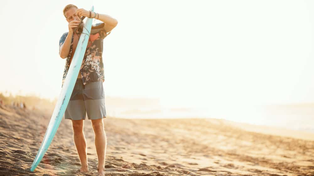 A man on the beach in board shorts attaching something to a surfboard