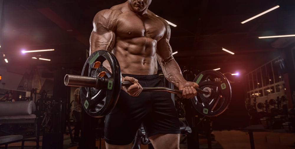 bodybuilder in the gym doing the exercise with dumbbells
