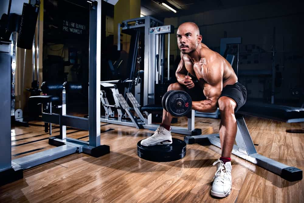 bodybuilder workout with dumbbells in gym