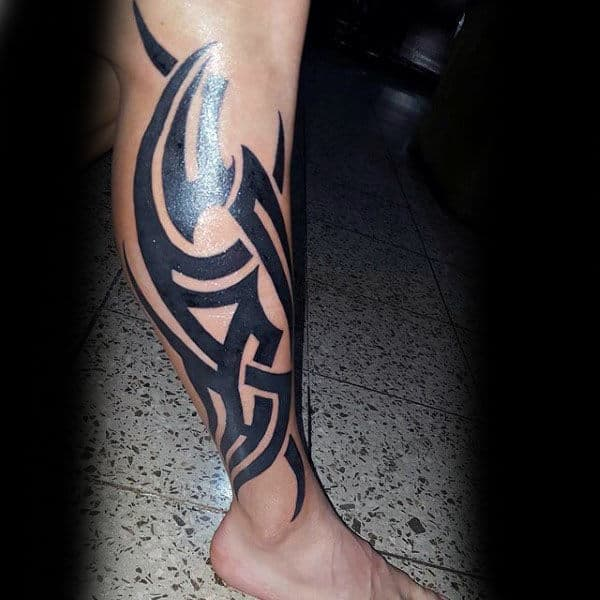 Bold Black Ink Tribal Tattoo On Males Leg