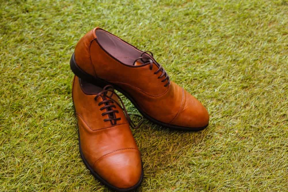 pair of brown oxford shoes, photographed on green grass