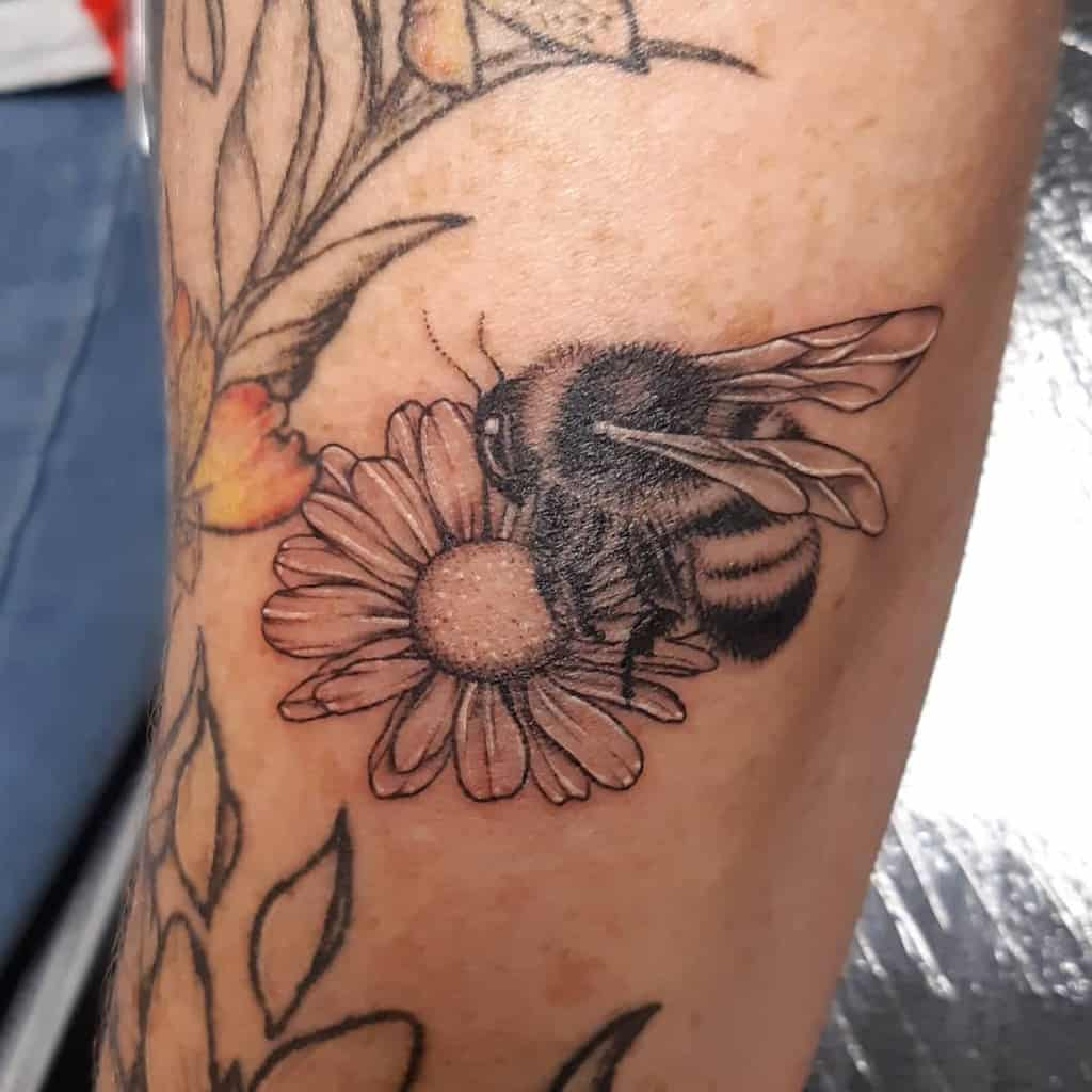 Forearm tattoo black and grey illustrative geometric design of bumble bee framed by daisies