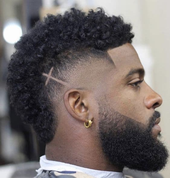 A burst fade haircut styled on curly hair and a cross design created on one side. A clean cut hairline continues to the beard