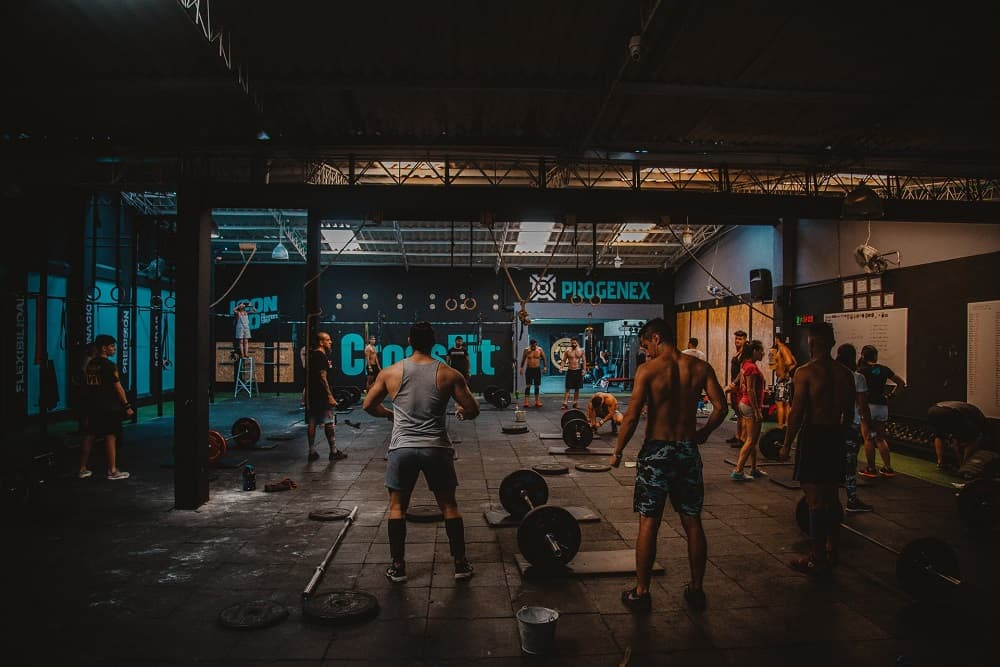 wide shot of a busy crossfit gym with different people doing exercises among scattered equipment