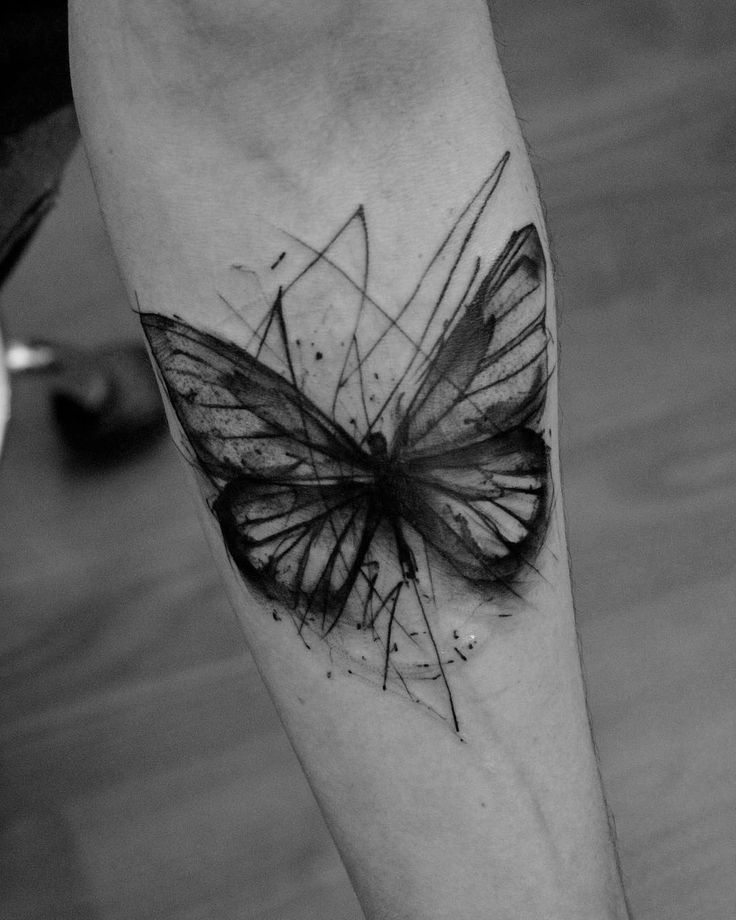 medium-sized black and grey geometric tattoo on man's forearm of surrealistic butterfly with messy lines around it