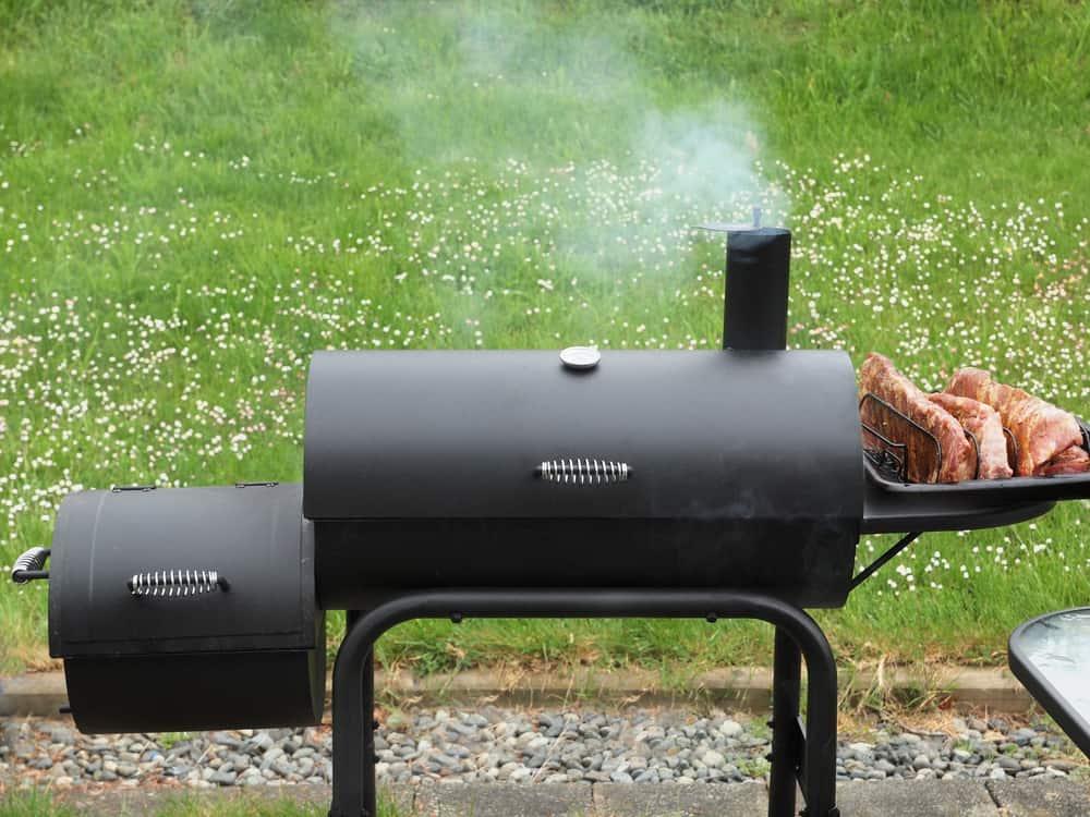 charcoal offset smoker at house backyard cookout