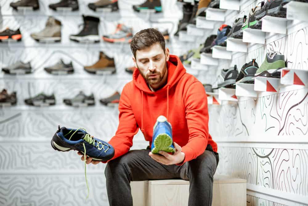 man choosing trail shoes in shop