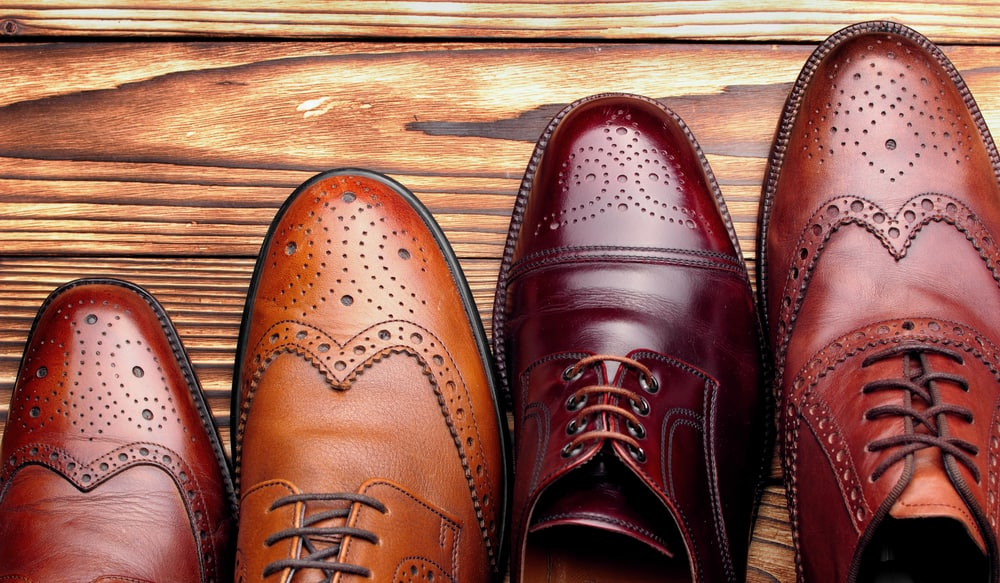 Four different men's brogue shoes in various colors