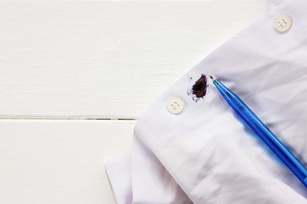 Ink,Stain,On,White,Shirt,With,Wooden,Table,Background,In