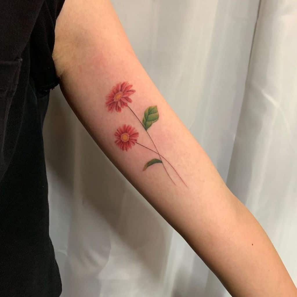 Bicep tattoo fine line color red green yellow delicate daisy
