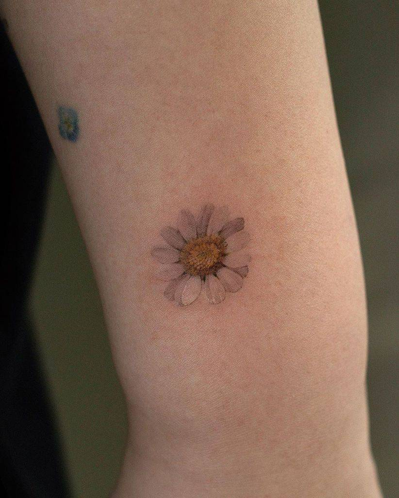 Wrist tattoo tiny color yellow and white daisy